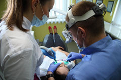 Dentist treating a patient`s teeth with dental tools in dental clinic. Dentistry. Royalty Free Stock Image