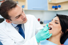 Dentist is treating teeth of the patient Royalty Free Stock Photos