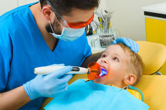 Dentist treats teeth of patient in dental clinic Stock Photos