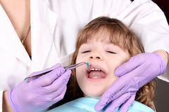 Dentist treats tooth little girl Stock Photo