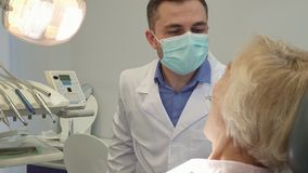Dentist turns on the dental light. Middle aged dentist turning on the dental light at the office. Close up of brunette caucasian doctor in procedure mask holding Stock Images