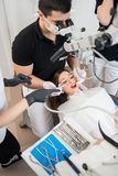 Dentist and two female assistants treating patient teeth with dental tools at dental clinic office. Dental equipment stock photography