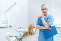 Dentist in uniform with clipboard in dental clinic with patient behind Stock Images