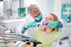 Dentist use dental light instrument for working Royalty Free Stock Images