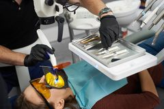 Dentist uses dental curing light for fixing patient`s teeth and takes another dental instrument from a tray stock photos