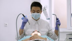 The dentist uses a drill for dental treatment. Dentist at work. On the background dentist assistant Stock Images