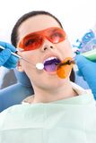 Dentist uses photopolymer lamp and dental mirror Stock Photos