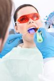 Dentist uses photopolymer lamp to treat teeth Royalty Free Stock Images
