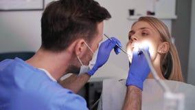 Dentist using dental drill and dental mirror. In dentist`s office stock footage