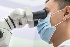 Dentist using a dental microscope stock images