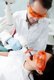 Dentist using laser Stock Image