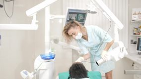 Woman dentist using x ray machine, patient lying on chair in dentistry. Young African American male with bad teeth. Dentist using x ray machine, patient lying on stock footage