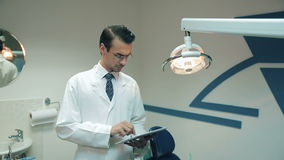 Dentist using tablet at the dental clinic