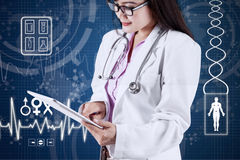Dentist using tablet with medical background. Young asian dentist working on tablet computer with futuristic medical background Stock Photo