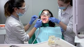 Dentist using water syringe. Female doctors working with patient stock footage