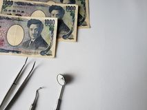 dentist utensils for oral review and japanese banknotes stock images
