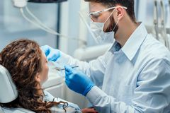 Dentist very carefully check up and repair tooth of his young female patient. Side view stock photo