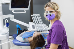 Dentist Wearing Loupes While Examining Young Patient In Clinic. Portrait of confident female dentist wearing loupes while examining young patient in clinic Stock Photo