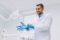 Dentist wearing medical gloves in dental clinic stock images