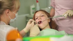 A dentist who did a tooth brushing in a teenager in a dental clinic stock footage