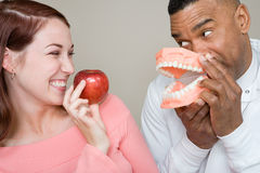 Dentist and woman holding an apple and false teeth royalty free stock images
