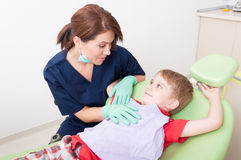 Dentist woman talking with kid patient Stock Photography
