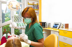 Dentist. At work checking young women Royalty Free Stock Image