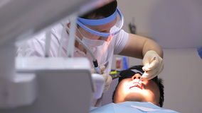 Dentist at work in dental unit with a nurse and a man lying patient. stock footage