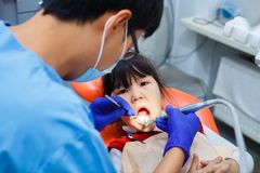 Dentist at work. Doctor cleaning little girl`s teeth, close up. Pediatric dentistry, prevention dentistry concept Royalty Free Stock Photo