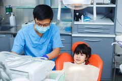 Dentist at work and his little young cheerful patient. Asian doc. Tor in medical mask working at dental clinic. Pediatric dentistry, prevention dentistry concept Stock Photo