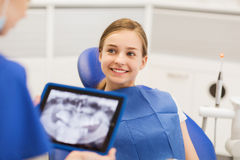 Dentist with x-ray on tablet pc and girl patient Stock Photos