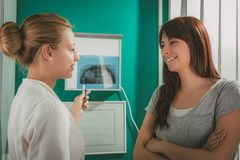 At The Dentist. Young female dentist showing to the patient X-ray picture in she`s office. Selective focus Royalty Free Stock Images