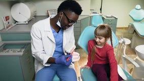 Dentista africano che insegna a poco paziente femminile a come pulire i denti sul modello di plastica archivi video