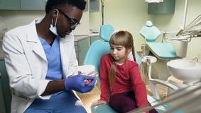 Dentista africano che mostra come pulire i denti sul modello di plastica al giovane paziente femminile video d archivio