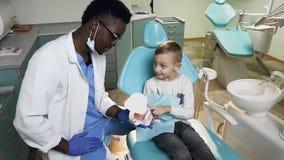 Dentista africano che mostra modello di plastica dei denti al piccolo paziente maschio stock footage