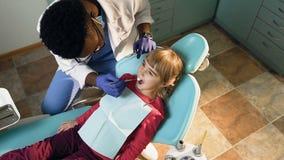 Dentista africano maschio che controlla i denti della bambina video d archivio