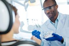 Dentista agradável que explica como escovar corretamente os dentes fotografia de stock