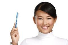 Dentista asiático novo de sorriso da mulher que mostra uma escova de dentes Fotografia de Stock Royalty Free