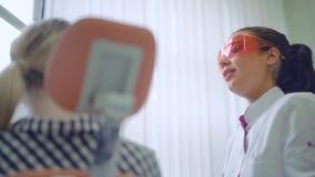 Dentista attraente che parla con il paziente della giovane donna alla clinica dentaria video d archivio