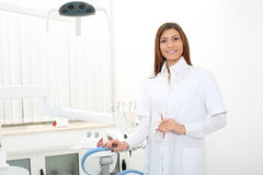 Dentista bonito da menina perto da cadeira dental que guarda glas da segurança Fotografia de Stock