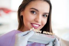 Dentista che controlla e che seleziona colore dei denti del ` s della giovane donna Fotografia Stock Libera da Diritti
