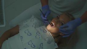 Dentista che controlla salute paziente bionda femminile della cavità con l'aiuto dello specchio Primo piano stock footage