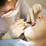 Dentista che cura un paziente femminile Immagini Stock