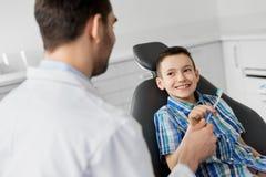 Dentista che dà spazzolino da denti al paziente del bambino alla clinica immagini stock