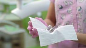 Dentista che disinfetta gli strumenti di odontoiatria Mani di medico che preparano attrezzatura dentaria stock footage