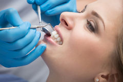 Dentista che esamina i denti di un paziente nel dentista fotografia stock libera da diritti