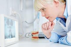 Dentista che esamina radiografia panoramica Fotografia Stock