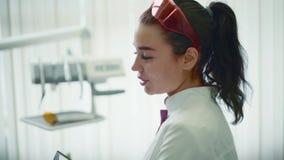 Dentista che explaning il suo lavoro ad un paziente in ufficio dentario archivi video