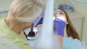 Dentista che fa pulizia professionale dei denti del paziente femminile in clinica dentaria video d archivio