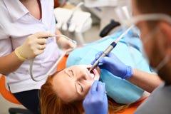 Dentista che inizia operazione comune di pulizia della bocca femminile immagini stock libere da diritti